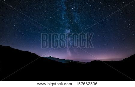 purple night sky stars. Milky way galaxy across mountains. Starry night sky