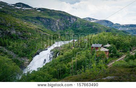 Kjosfossen waterfall valley landscape. Waterfall dam, village houses and famous Flamsbana railway. Flam, Aurland, Norway.