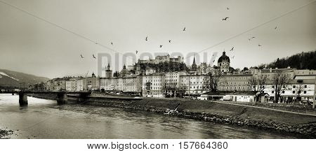 Beautiful view of Salzburg skyline with Festung Hohensalzburg and Salzach river in winter - Black and white version