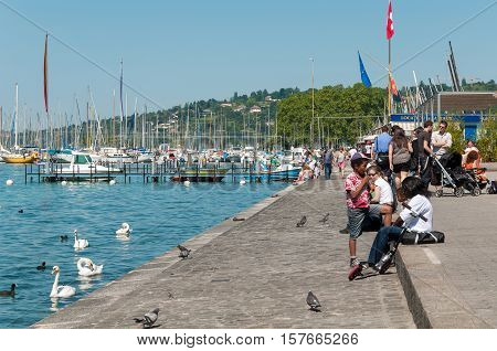 GENEVA, SWITZERLAND - JUNE 5, 2010 - People enjoying summer at lake Geneva (Le Léman), in the harbor of Geneva, Switzerland