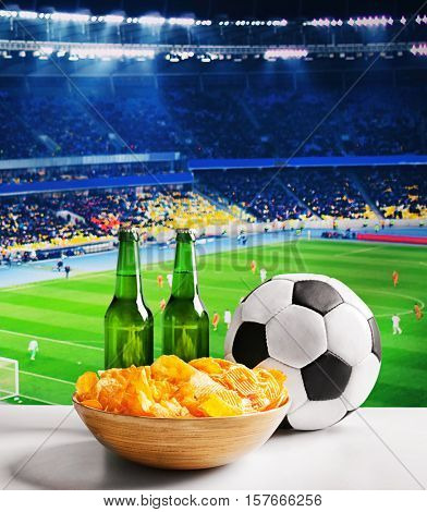 Beer with snack and ball on table against football field background. Sport and entertainment concept.
