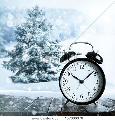 Alarm clock on wooden table against beautiful snowy landscape. Daylight saving time concept.