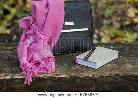 women's accessories - leather black bag neckerchief and notebook on dark wooden surface
