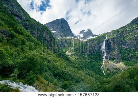Dreamy mountain valley with green forests, rocks and waterfalls. Hiking path to Briksdalsbreen glacier. Briksdal, Norway.