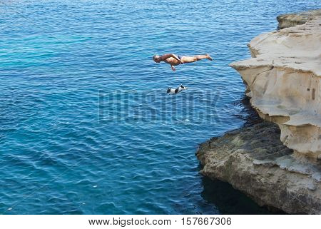 St Peter Pool Bay, MALTA-dec 8: man and dog jumping  into the the water in St Peter Pool bay in Malta on Dec 8, 2015.Two crazy friends dog and man jumping to swim in the sea. Active man