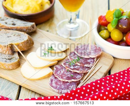 Salami smoked cheese cherry tomatoes and crisps for tapas poster