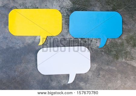 Three of Yellow Blue and White Speech Bubbles Over Gray Grunge Background - Balloon speech bubble concept