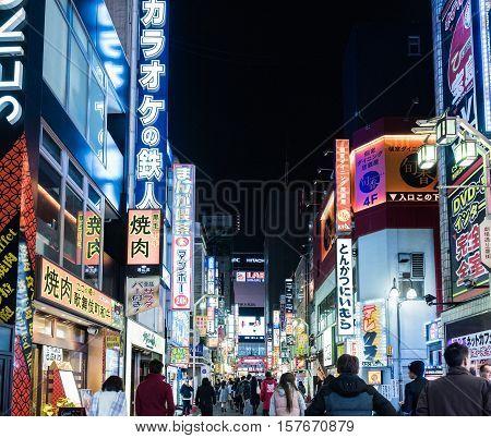 Tokyo, Japan - December 6, 2015: Pedestrians walking in the neon light streets of Shinjuku, Tokyo, Japan at night