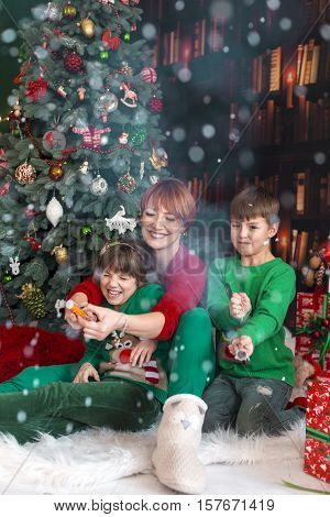 Mother and her kids having fun with petards near dressed up tree