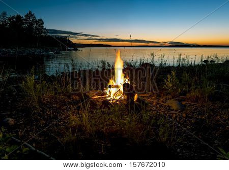 The bonfire is lit on the shore of the lake on a background picturesque sunset