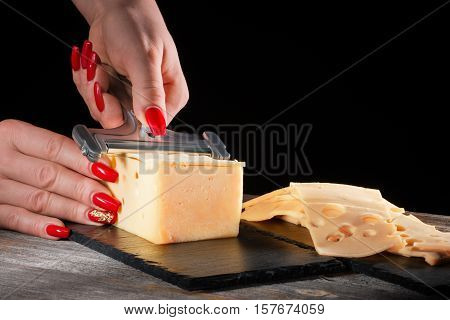 Female hands with beautiful bright manicure cut cheese whetstone by means of a cheese slicer on a black slate plate in style a rustic