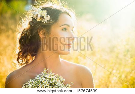 Innocent Young Girl Outdoors at Nature Background. Fashion Wedding Hairstyle and Accessories. Beautiful Woman Portrait. Candid Bride Photo. Sunset Backlit Light. Toned Photo with Copy Space.