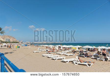 Alicante, Spain - September 9, 2016; Beach-goers enjoyng hot summer day at Postiguet Beach Alicante Spain street and building scene