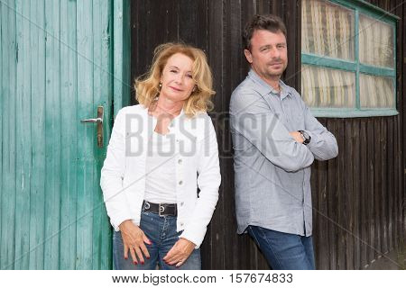Mature Couple Standing Against An Old Wooden Faraway Look