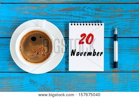 November 20th. Day 20 of month, loose-leaf calendar and white coffee cup at blue wooden workplace background. Autumn time, top view.