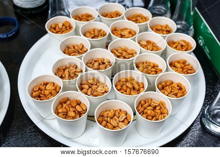 Paper cup of fresh roasted salted peanuts or groundnuts on an dark table or bar counter