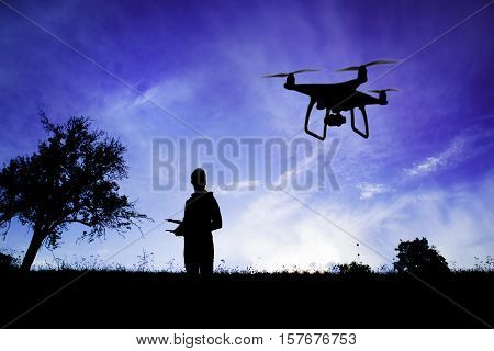 Silhouette of young man with flying drone in nature at dusk against blue sky.