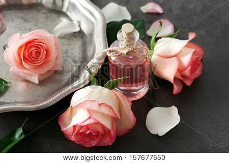 Metal plate with aroma oil and roses on table