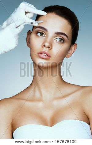 Beautiful woman face and beautician hands with syringe. Doctor makes cosmetic injection in forehead. Clean Beauty concept