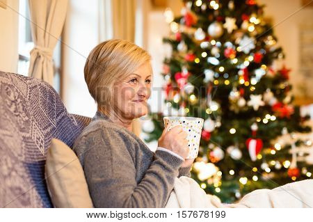 Beautiful senior woman sitting on couch in front of illuminated Christmas tree inside in her house enjoying cup of tea or coffee, smiling.