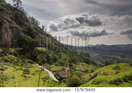 Ooty India - October 25 2013: Panoramic scenery of the Nilgiri hills shows forest many hills at horizon free floating stormy clouds rocks a road and a farm. Shades of green. Shot from us a hill.