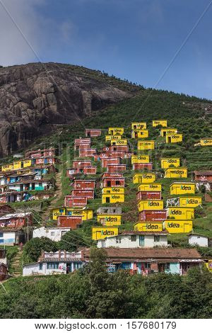 Ooty India - October 25 2013: Valparai village looks like a favela built on the of a hill. Bright yellow and wine red houses for poor people sponsored and painted by Idea and Vodaphone. Blue sky rocky hill green foliage people.