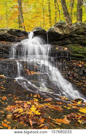 Water splashes down a small rocky cliff adorned with autumn leaves in Indiana's Lieber State Recreation Area.