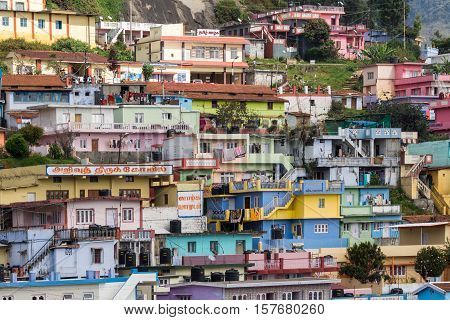 Ooty India - October 25 2013: Colorful collection of houses built close together above each other on a near Wellington Contonment along road 181. People cars laundry business.