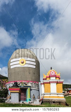 Ooty India - October 25 2013: Shiva shrine near Valparai village in the form of giant Shivalingam on top of circular construction. Blue and white cloudy sky. Houses in far background on hill. Statues on shrine.
