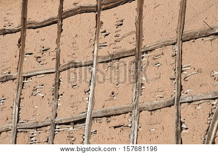 Wall of rustic barn with wooden strut and adobe mortar as background