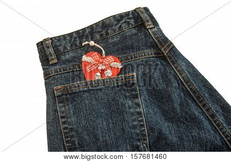 Jeans with handmade wooden red Christmas heart with ribbon and bells in pocket. Isolated over white.