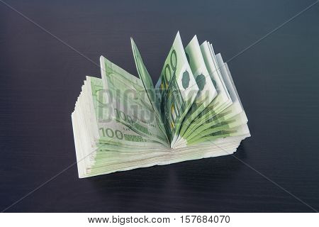 Pile of money hundred euro bills stacked open on table shaping an arc blue light coming from top right corner