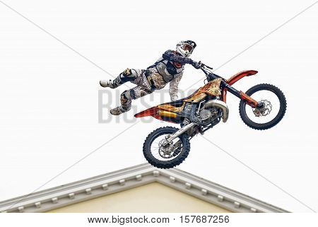 Tyumen, Russia - June 10, 2009: Red Bull X-Fighters Exhibition Tour. Freestyle Motocross. Sportsman carries out a trick over city Drama theater background