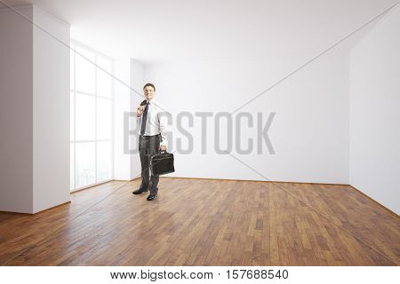 Businessman in unfurnished interior with blank wall
