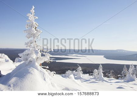View of the lake with mountain range Zyuratkul winter landscape. Snow swept spruce