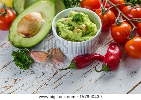 Guacamole sauce and indredients on wood background, copy space
