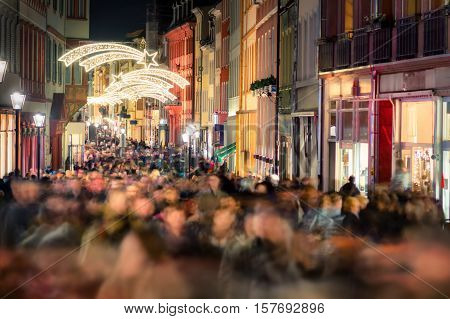 Large crowd of people hustling and shopping in a pedestrian area in Heidelberg Germany for Christmas