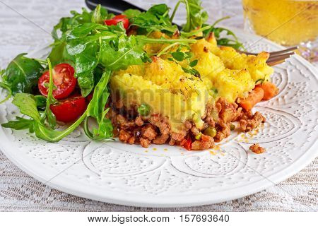 Traditional british shepard pie on plate with salad.