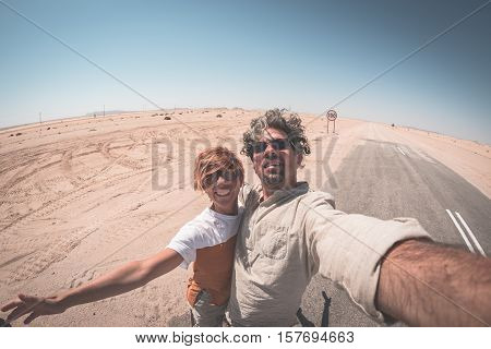 Adult Couple Taking Selfie On Road In The Namib Desert, Namib Naukluft National Park, Main Travel De