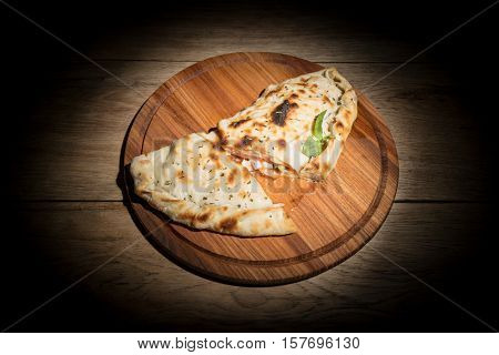Delicious fried cheburek with leaked oil cut into pieces and served on a wooden plate in the dark