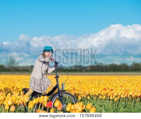Happy smiling kid riding a bike in a yellow tulips field on a sunny day