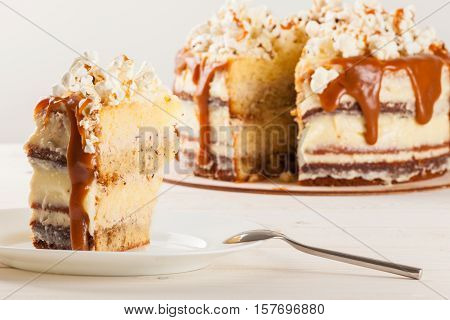 Homemade cake with hazelnuts and salty caramel with vanilla - hazel shortcakes and delicate hazelnut cream, decorated with salty popcorn. Cut a piece of cake on a plate.