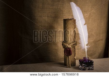 Literature concept. Old inkstand with feather near scroll and on canvas background.