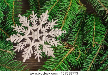 Christmas wooden natural background with branches of fir trees and wooden snowflakes and stars
