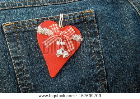 Red wooden Christmas heart with ribbons and bells hanging on back pocket of jeans.