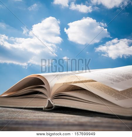 book open read legal wisdom novel sky cloud life background light old space wooden concept page religion blue concept - stock image