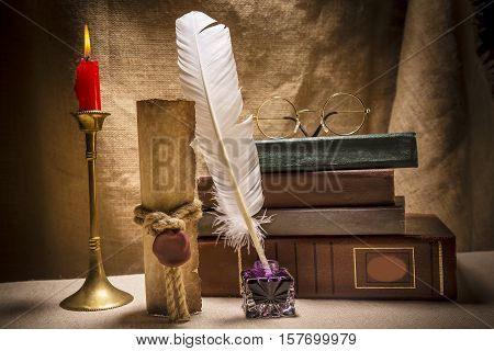 Vintage still life with glasses on old books near inkstand feather old paper and burning candle on canvas background.
