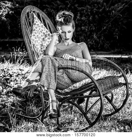 Outdoors portrait of beautiful young woman which sitting in rattan rocking-chair in evening summer garden. Black-white photo.