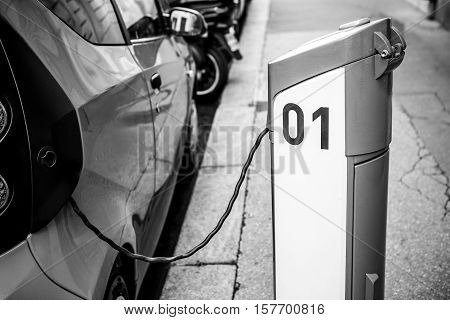 Power supply for electric car charging. Electric car charging station. Close up of the power supply plugged into an electric car being charged. Black-white photo.
