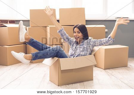 Beautiful girl is raising hands looking at camera and smiling while sitting in the box ready to move